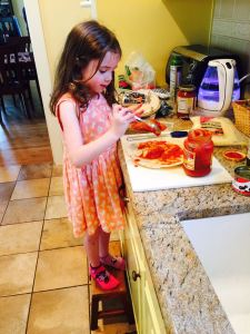 Molly in mismatched socks making her pizza.